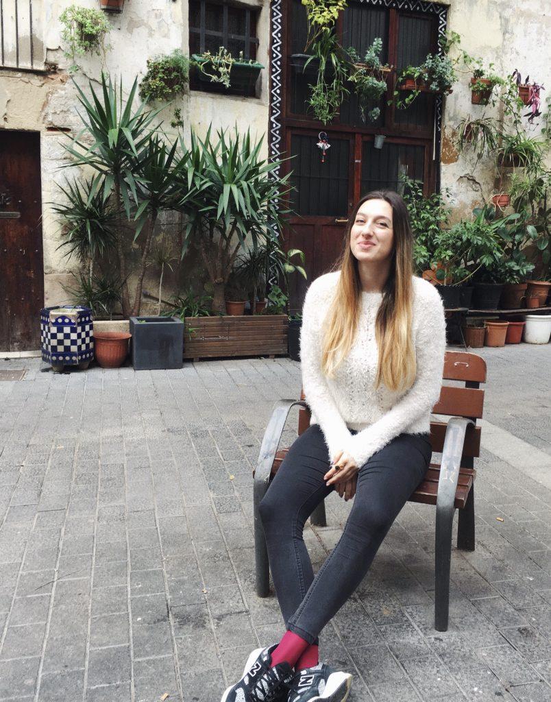 момиче, седнало на дървен стол и заобиколено от цветя