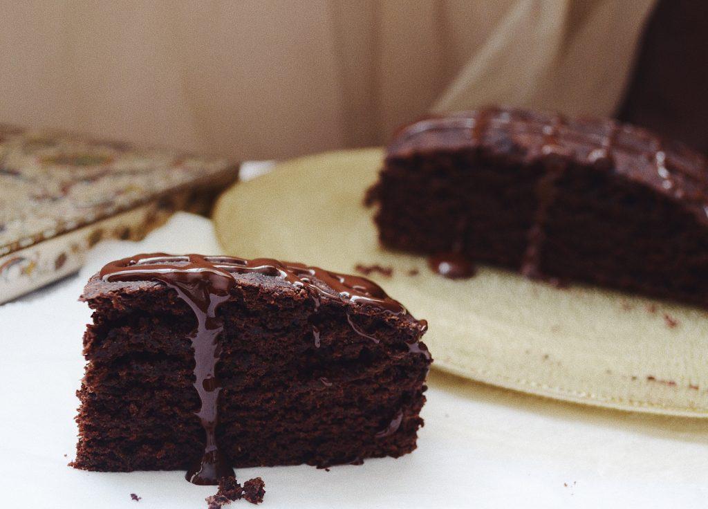 парче какаов кекс и златна чиния на заден фон