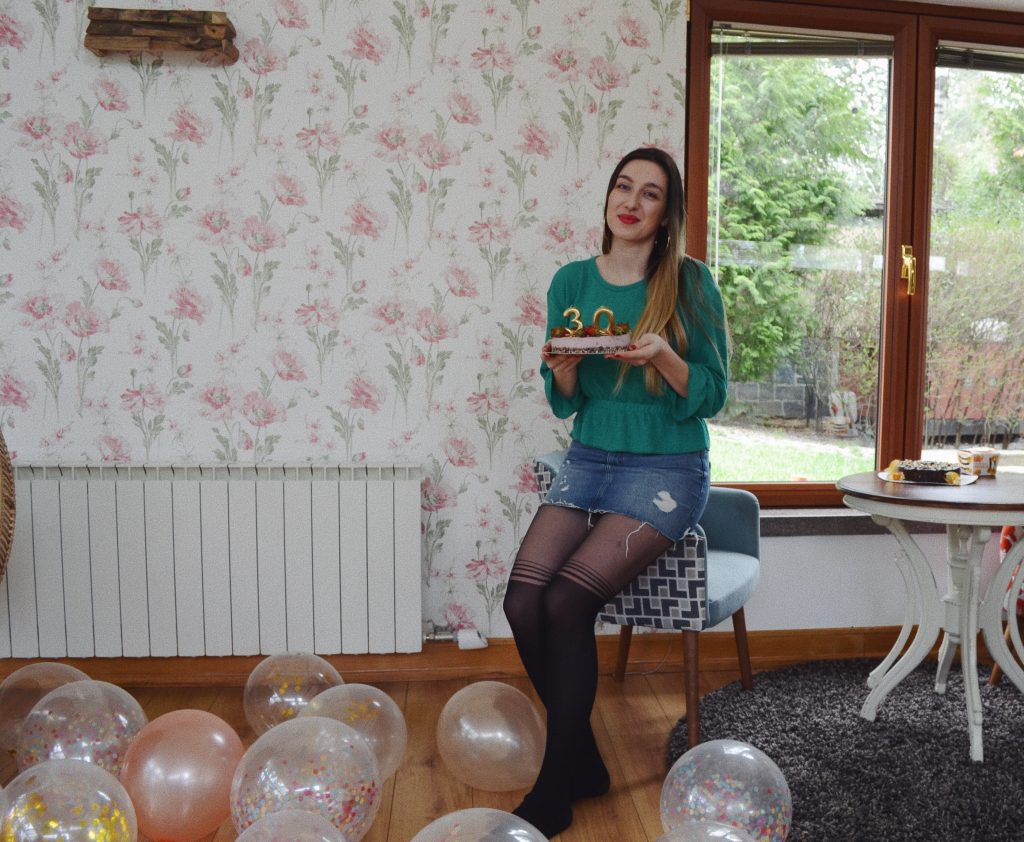 girl with a cake sitting on a couch and balloons on the floor