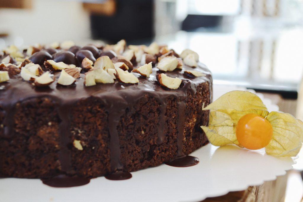 one side of a chocolate cake with hazelnuts