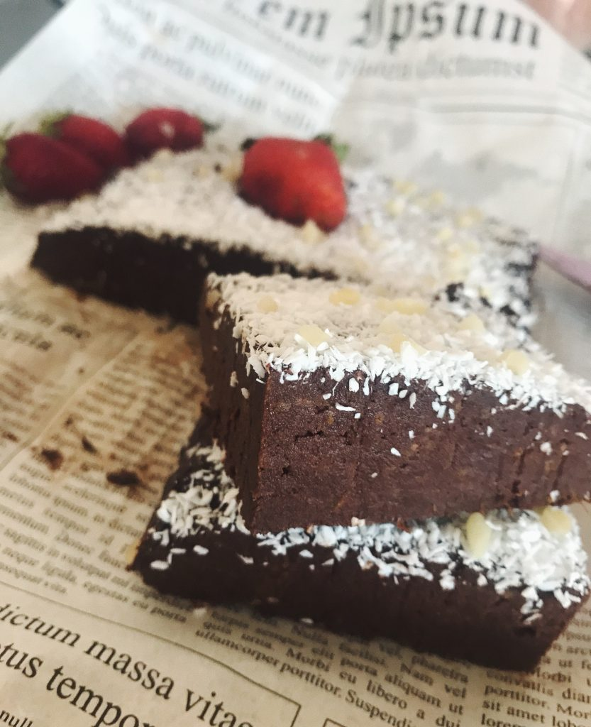 sliced cocoa brownie with straberries and coconut